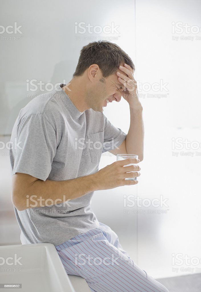 Man with headache drinking water royalty-free stock photo