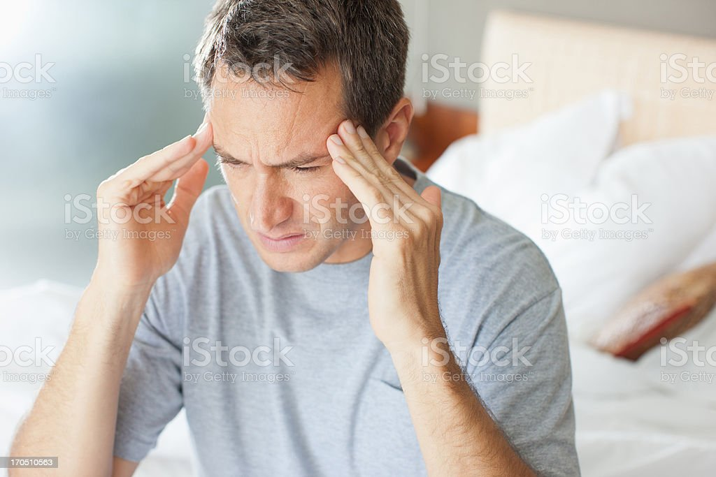 Man with headache rubbing forehead stock photo
