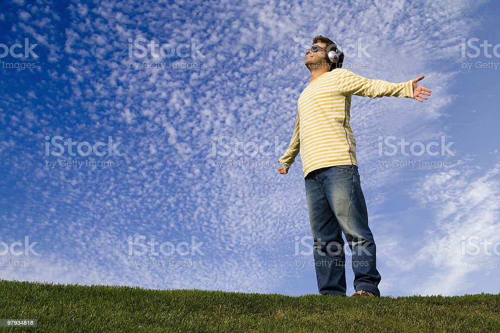 Man with headphones and arms outstretched standing on hill stock photo