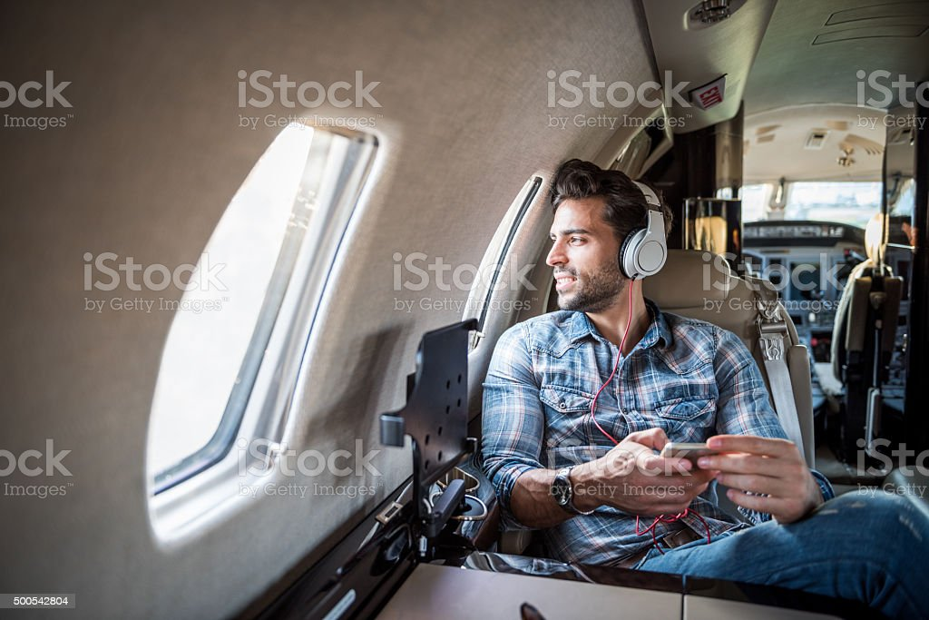 Man with headphones inside private jet airplane stock photo