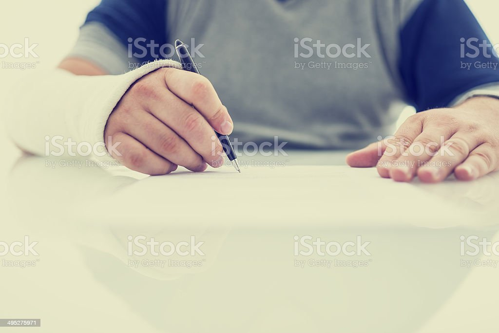 Man with his arm in a plaster cast writing stock photo