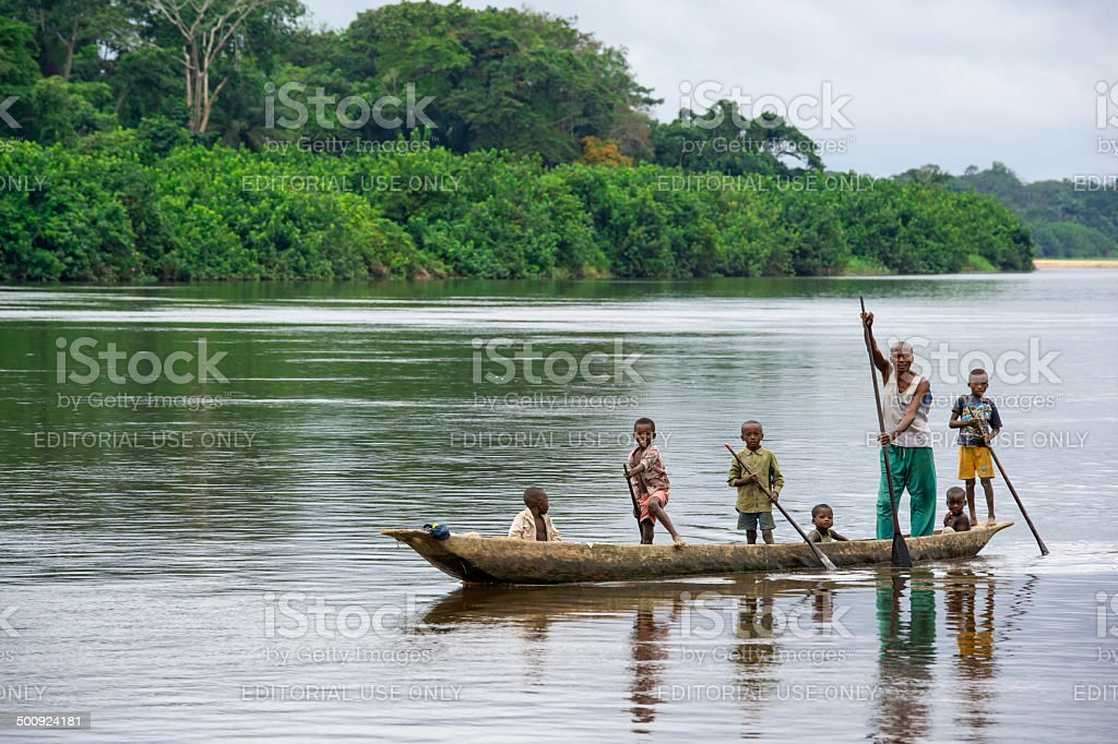 Man with his children in a pirogue on Congo River stock photo