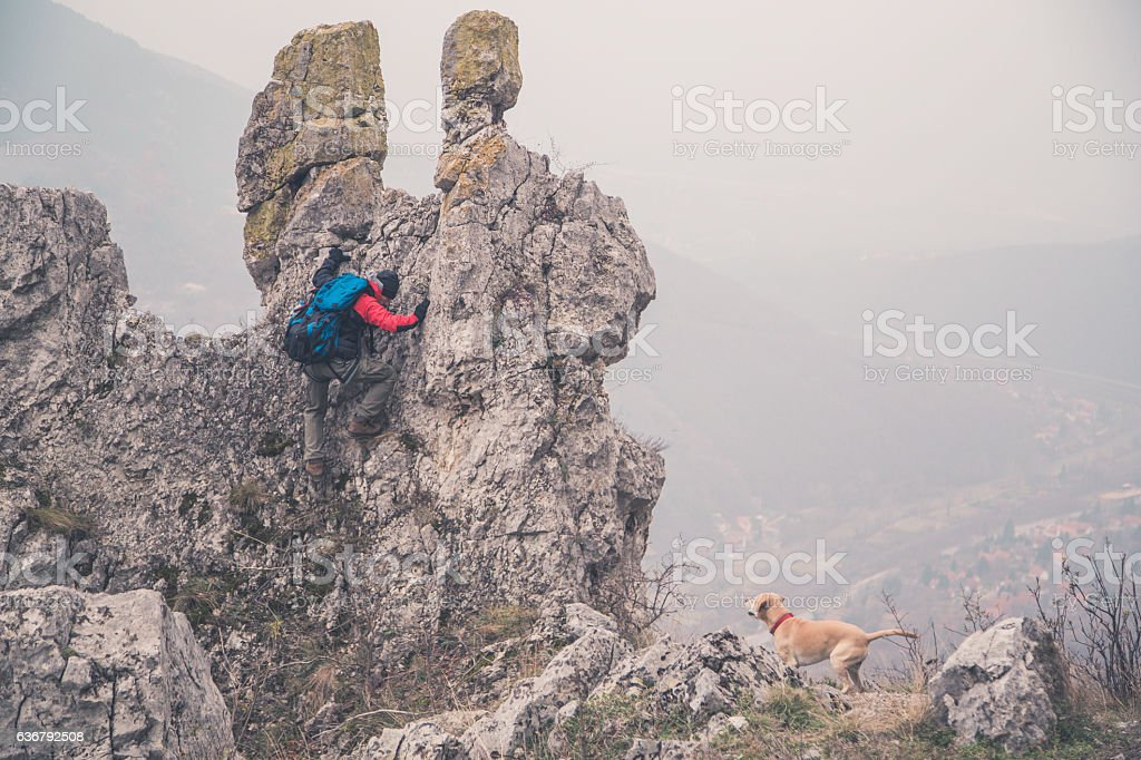Man with his dog hike in mountain. stock photo
