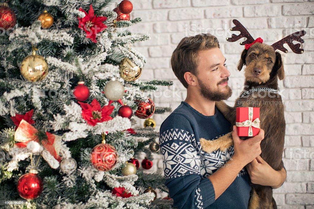 Man with his dog hugging for christmas. stock photo