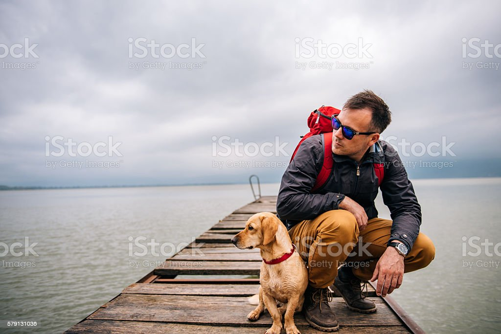 Man with his dog sitting on dock stock photo