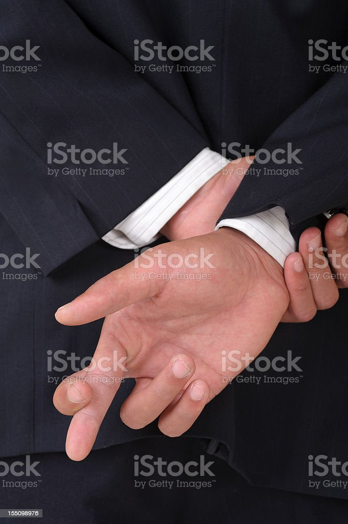 A man with his fingers crossed behind his back stock photo