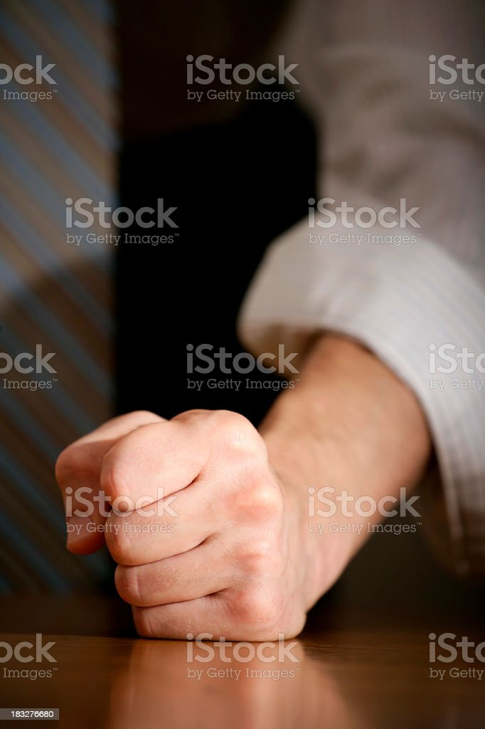A man with his fist on the desk for determination stock photo