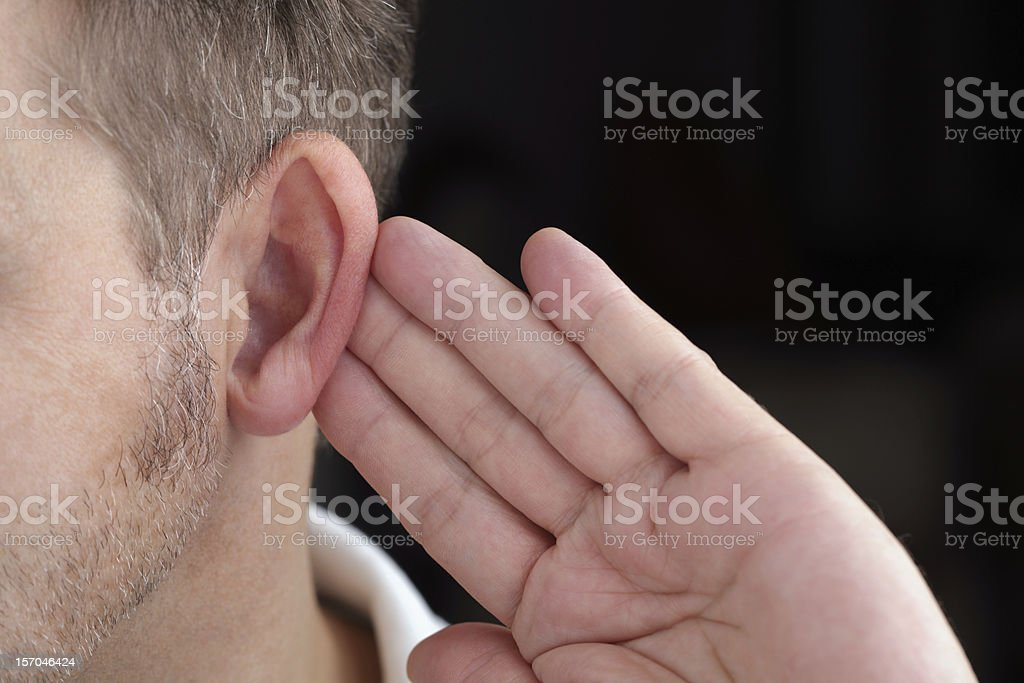Man with his hand behind his ear trying to hear stock photo