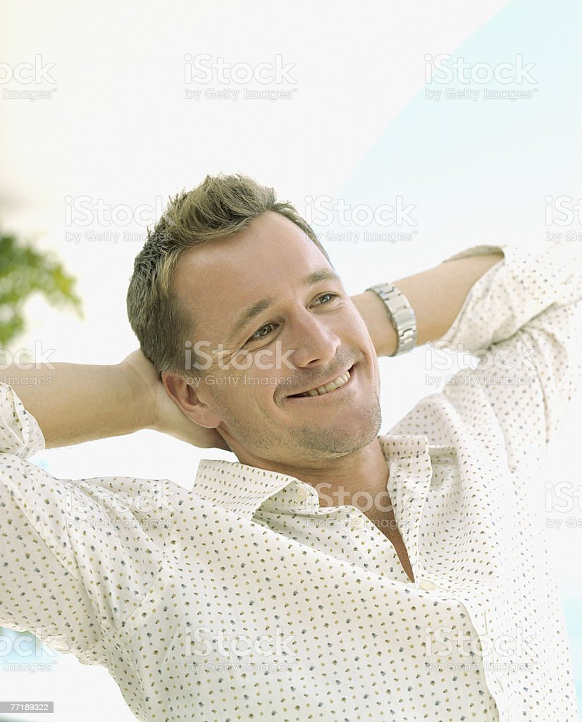 A man with his hands behind his head relaxing royalty-free stock photo