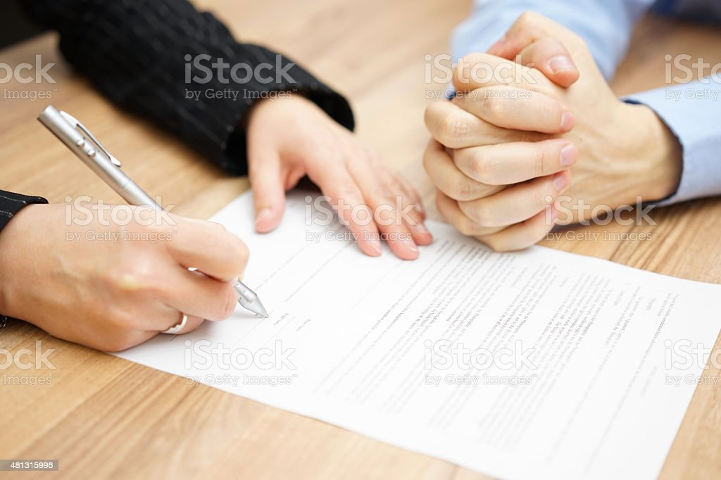Man  with his hands clasped is waiting woman to sign stock photo