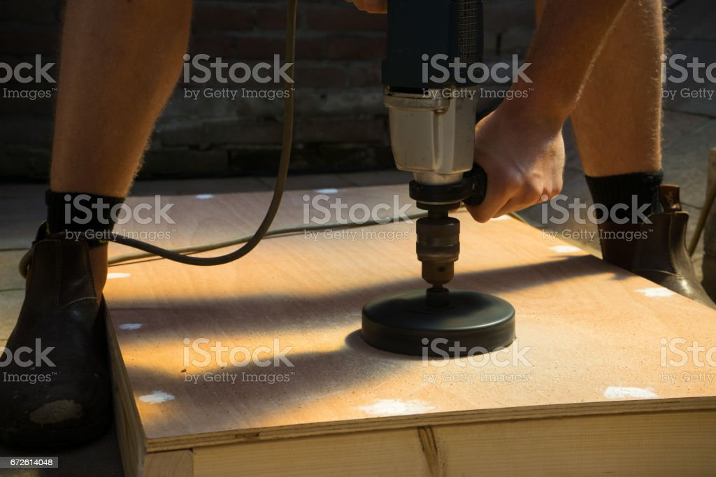 Man with Hole Saw Cornhole Board DIY stock photo