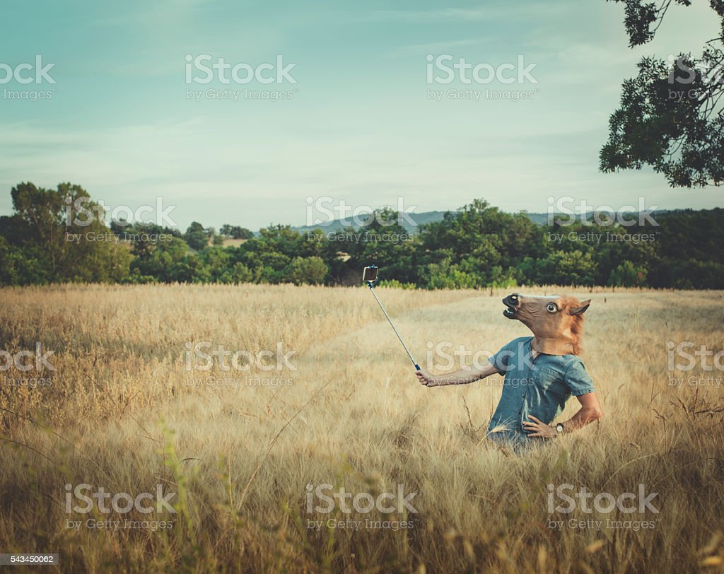 Man with horse head takes a selfie in a field stock photo