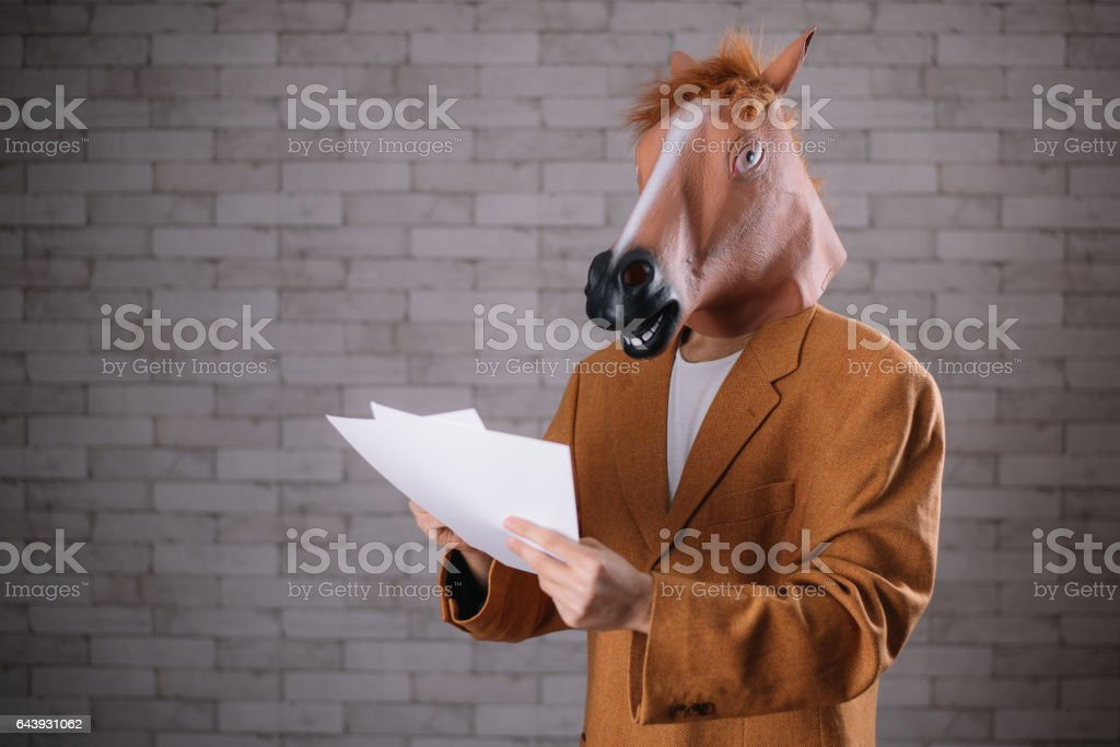 Man with horse mask browsing through papers stock photo