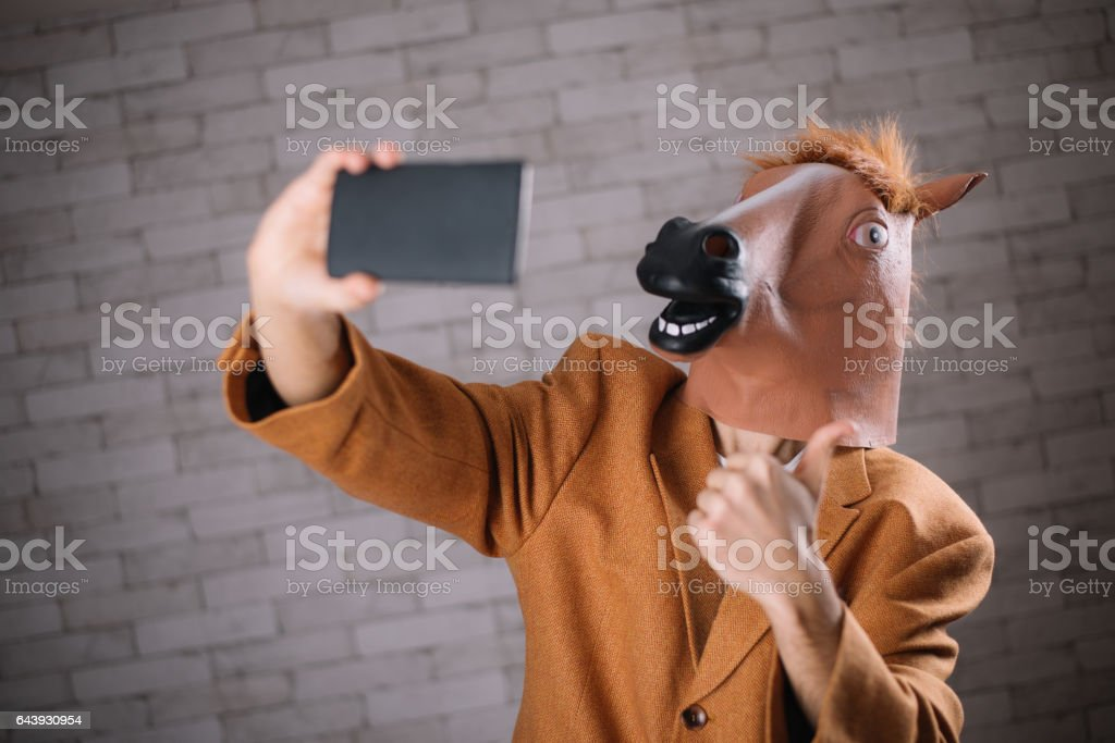 Man with horse mask taking a selfie stock photo