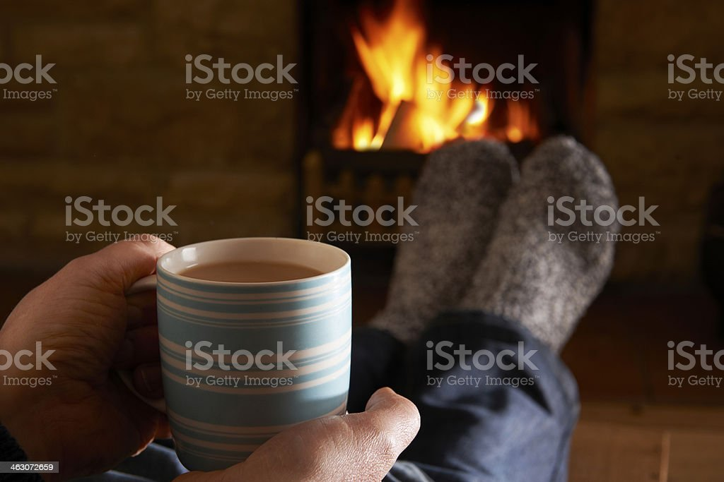 Man With Hot Drink Relaxing By Fire stock photo