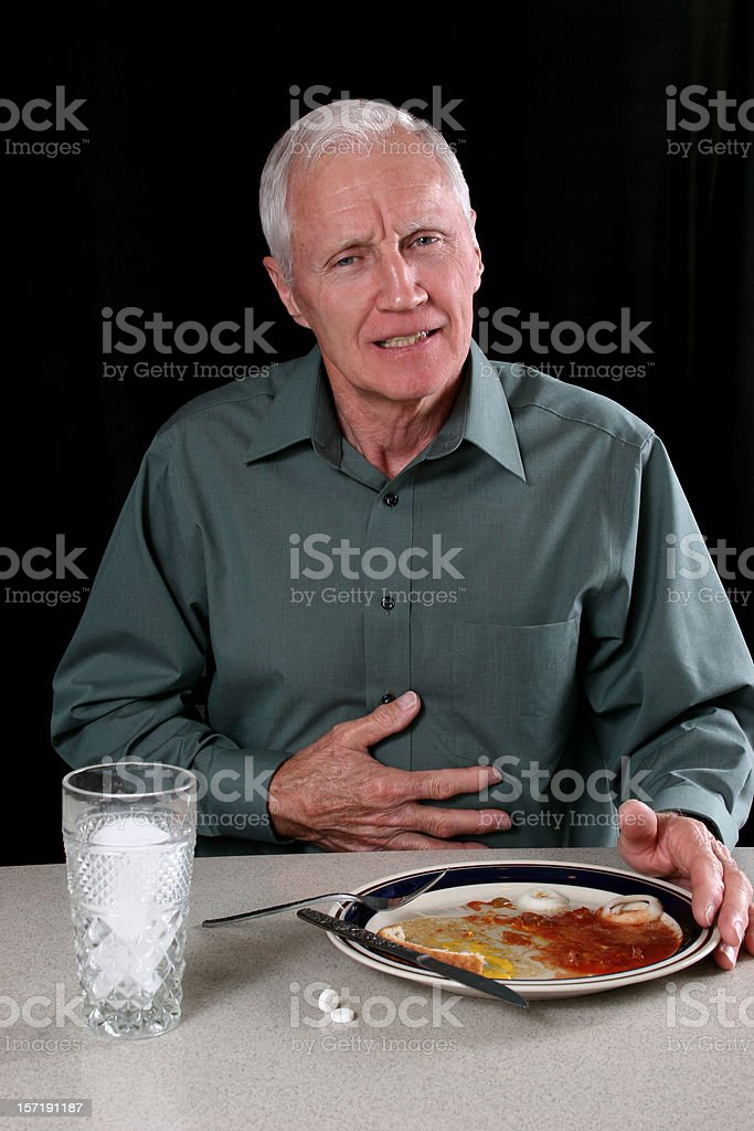 Man with indigestion after meal. Pushing away plate. Dinner table. stock photo