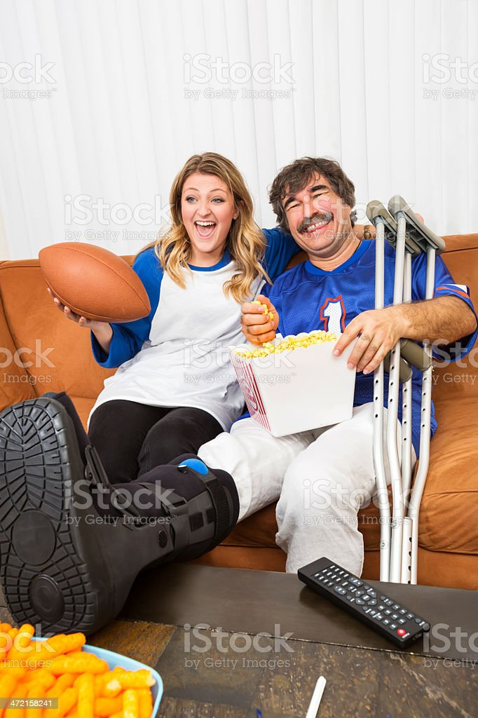 Man with injured leg and his girlfriend watching football royalty-free stock photo