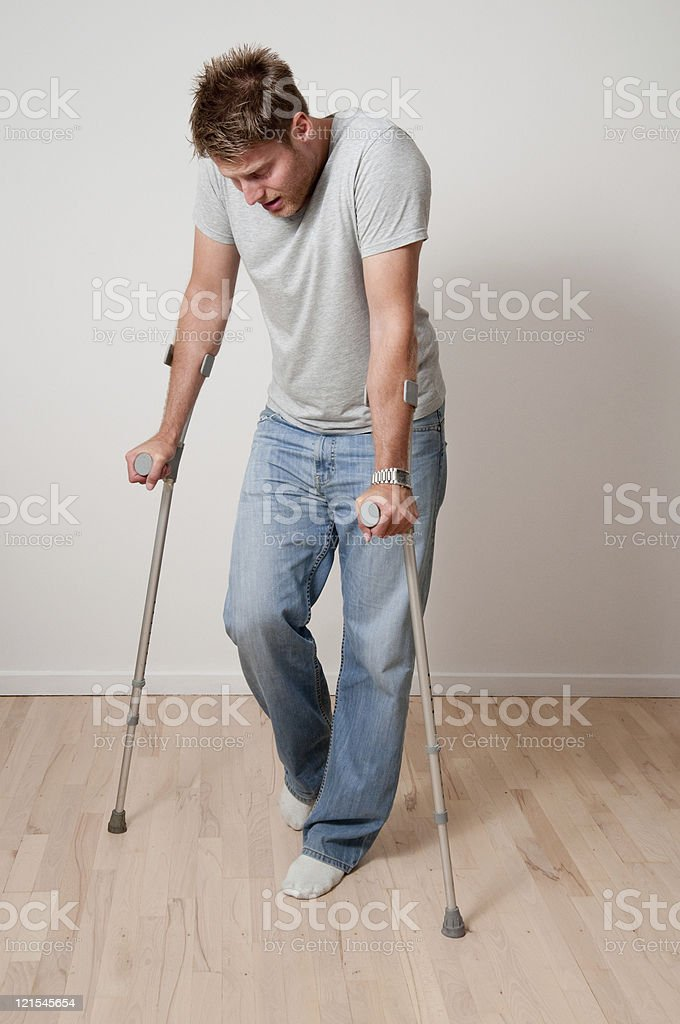 Man using crutches stock photo