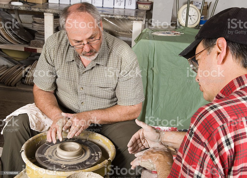 Man With Instructor Learning To Use a Potter's Wheel stock photo