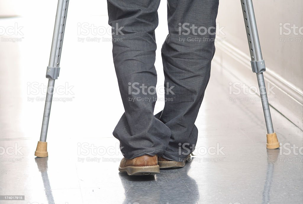 Man with jeans and brown loafers walks using crutches royalty-free stock photo