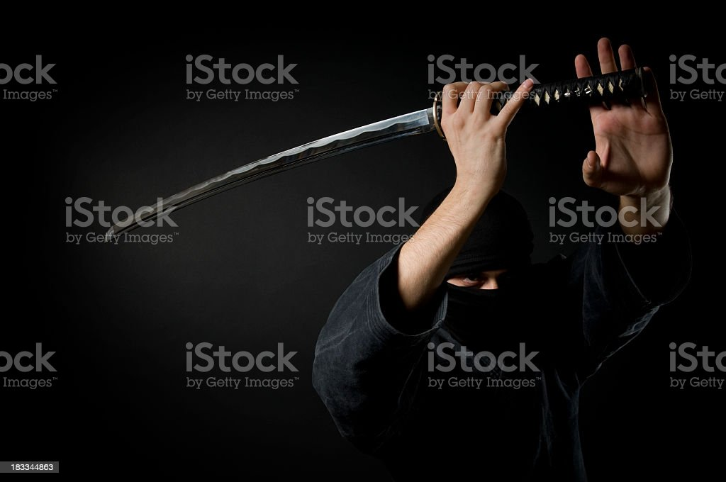 Man with katana, black background stock photo