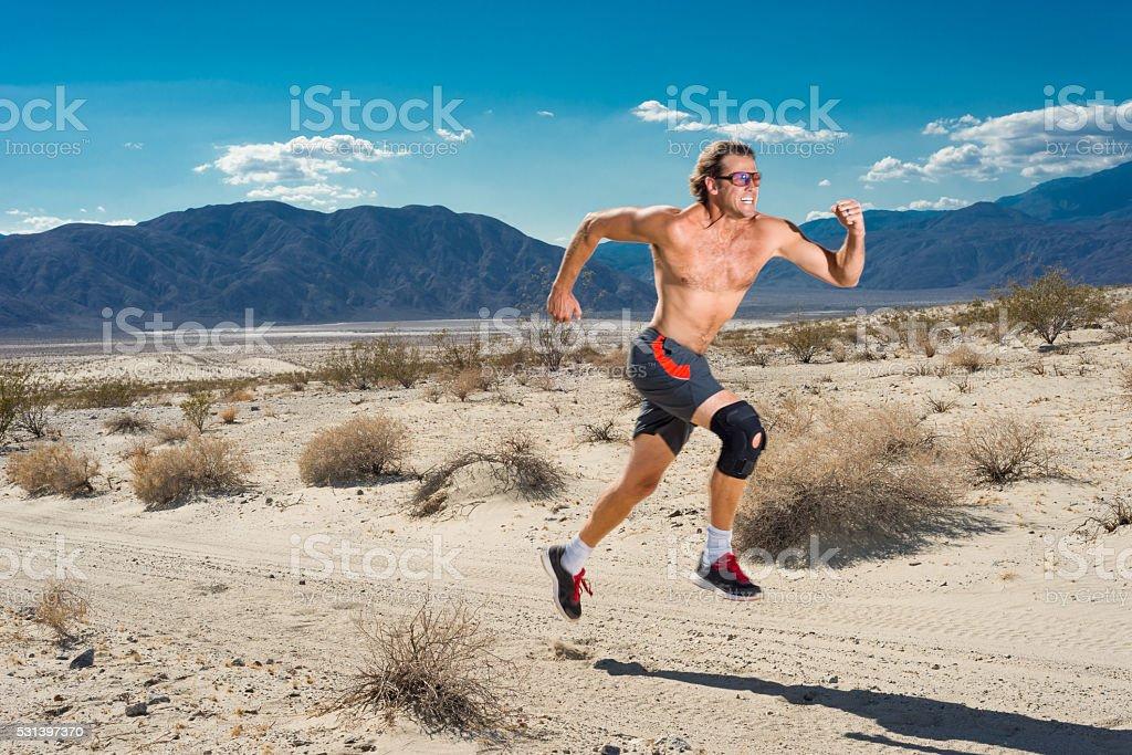 Man With Knee Brace Running In The Desert stock photo