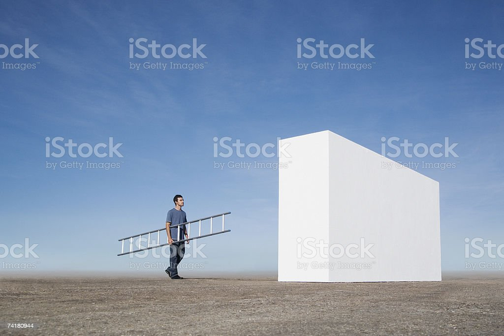 Man with ladder approaching wall outdoors royalty-free stock photo