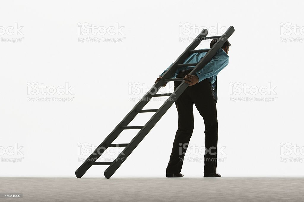Man with ladder leaning against his back stock photo