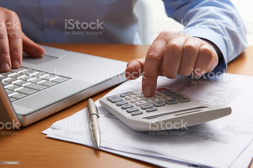 Man with laptop and calculator working on finances at desk stock photo