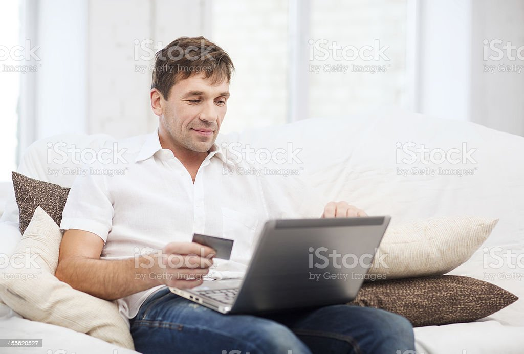 man with laptop and credit card at home stock photo