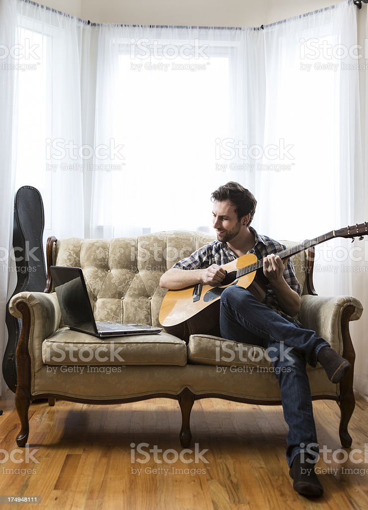 Man with Laptop and Guitar stock photo