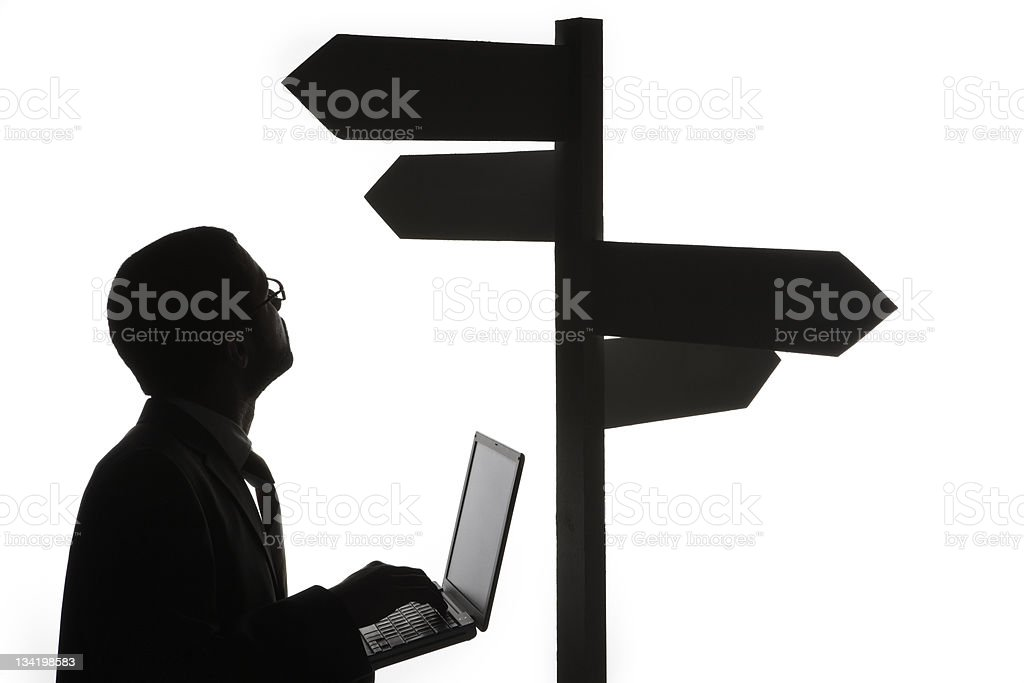 Man with laptop and sign post stock photo