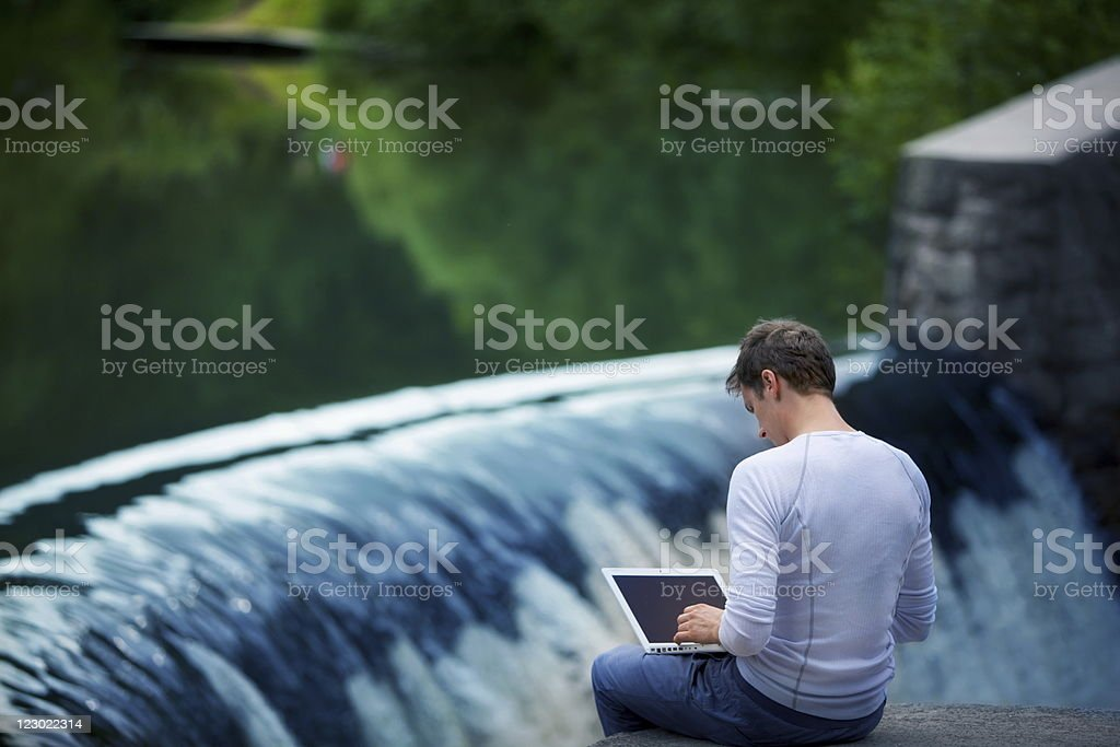 man with laptop at the river over waterfall stock photo