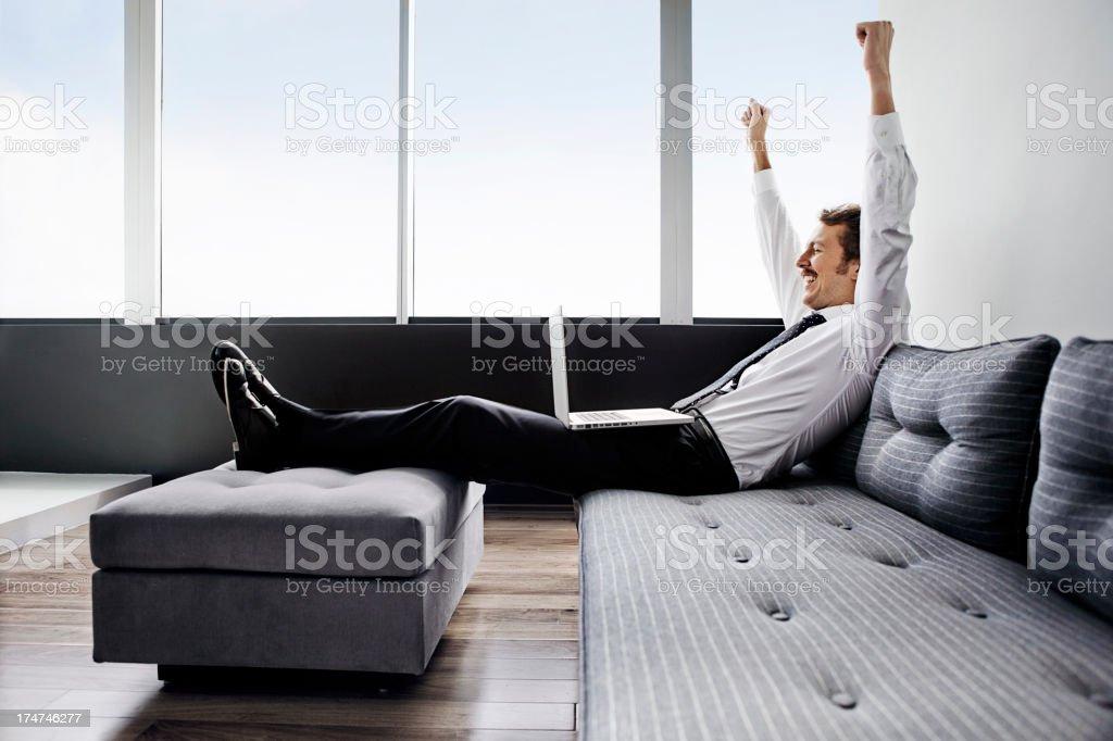 Man with laptop celebrating on sofa royalty-free stock photo