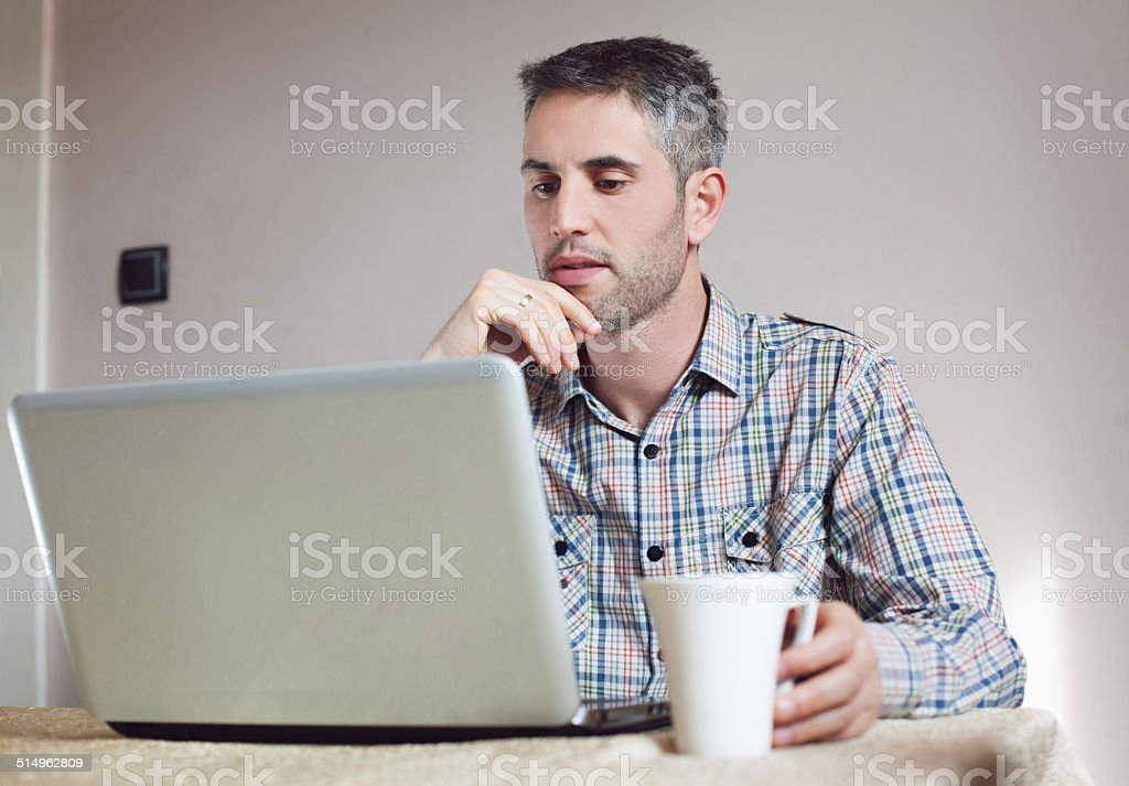 Man with laptop in the house stock photo