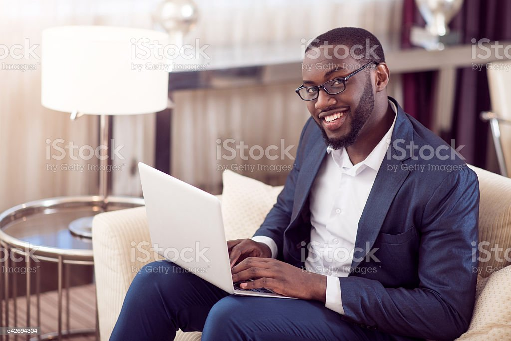 Man with laptop looking at camera stock photo
