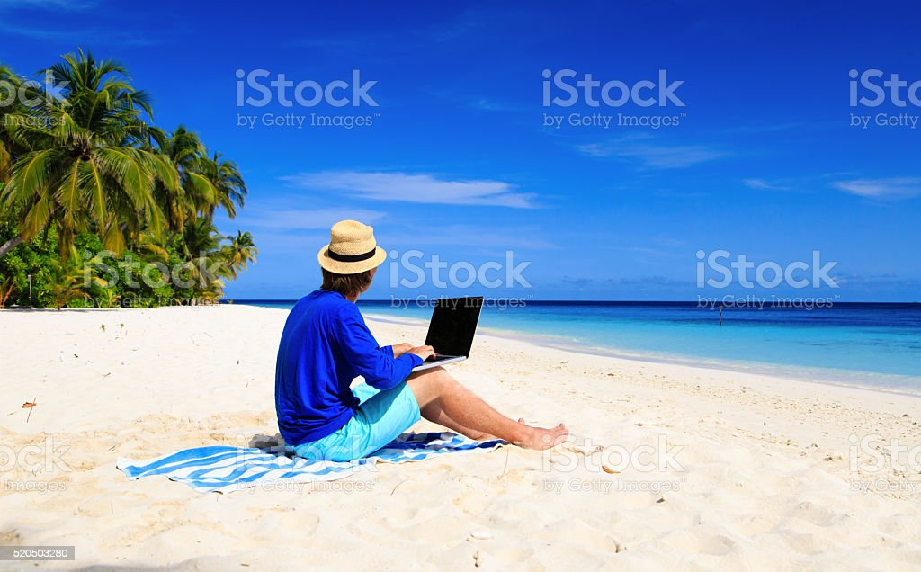 man with laptop on tropical beach stock photo