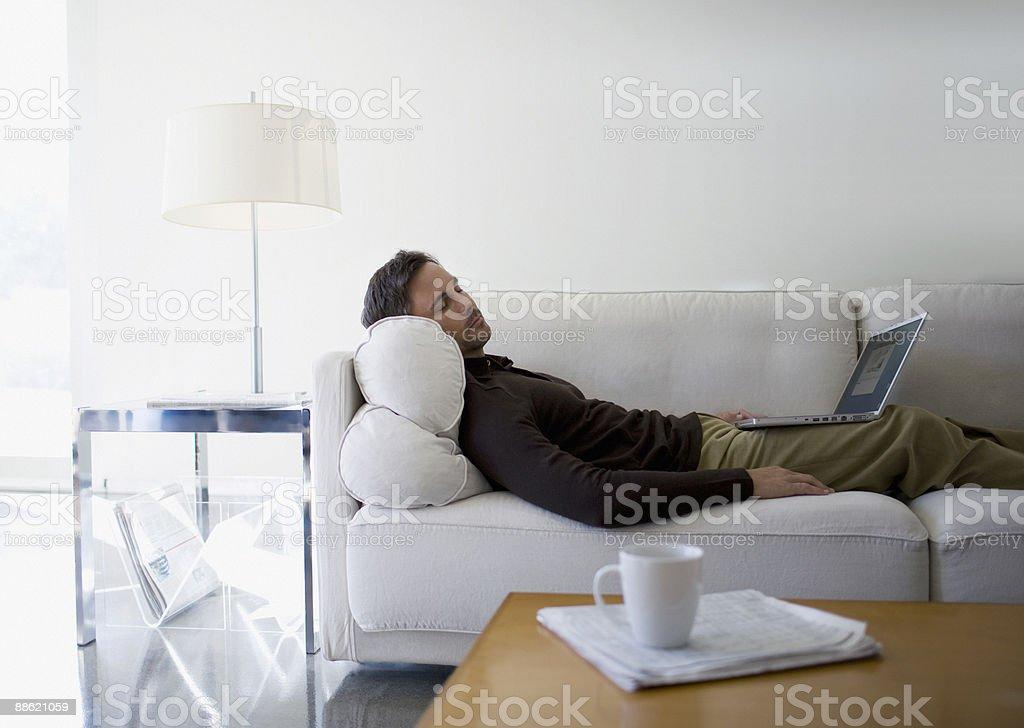 Man with laptop sleeping on sofa royalty-free stock photo
