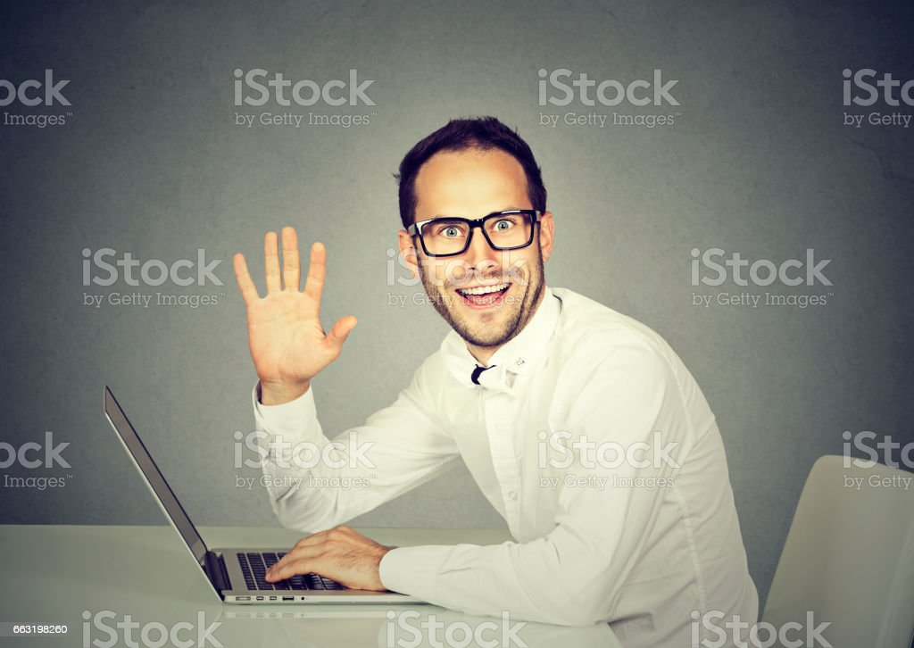 Man with laptop waving with hand saying hi to camera stock photo