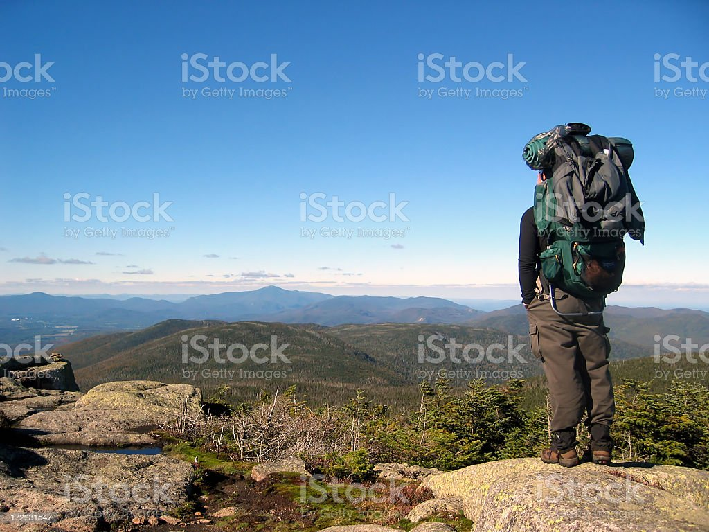 A man with large backpack standing atop a mountain stock photo