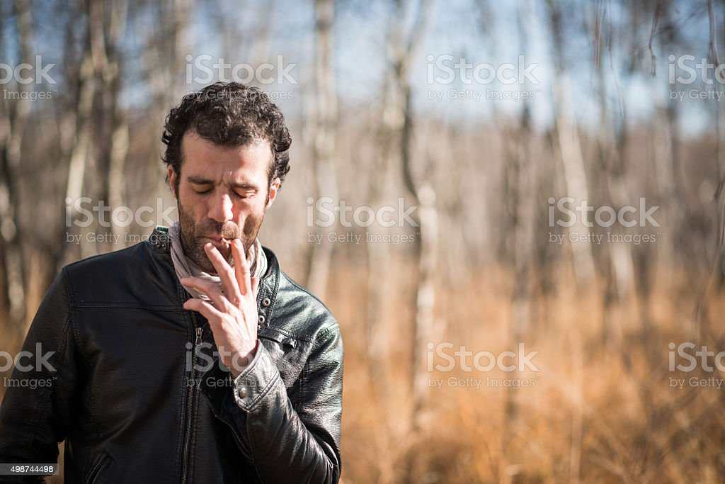 Man with leather jacket and jeans in nature in autumn stock photo