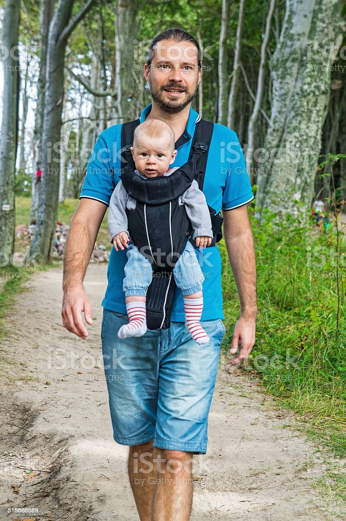Man with little baby boy in child carrier on walk stock photo