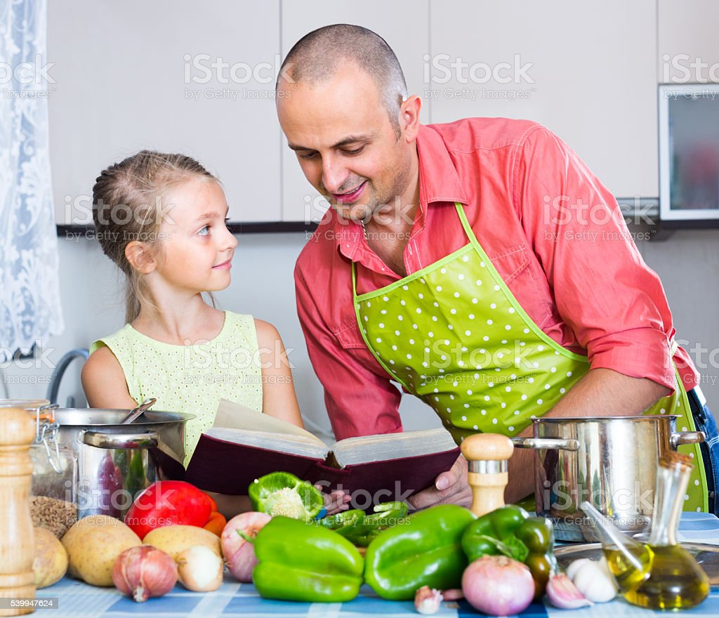 Man with little daughter at kitchen stock photo