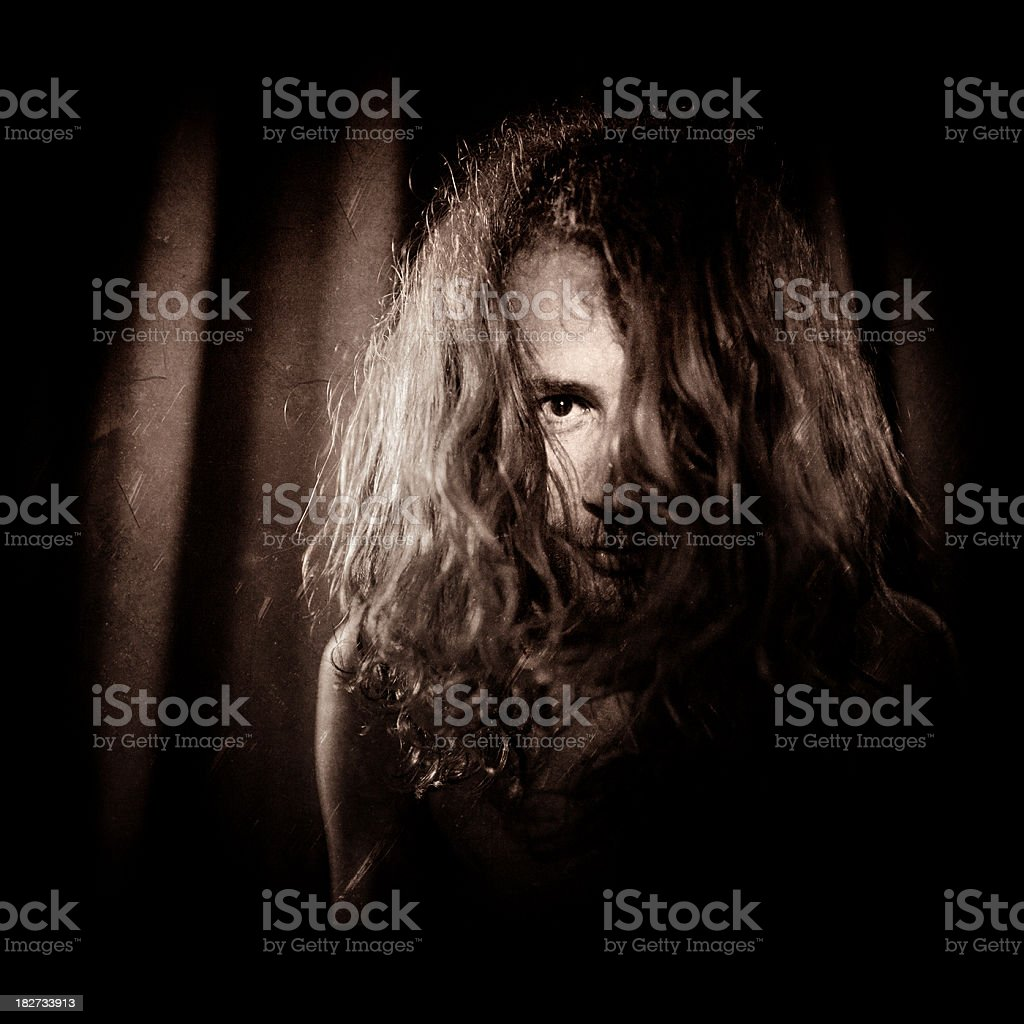 man with long hair covering his face stock photo