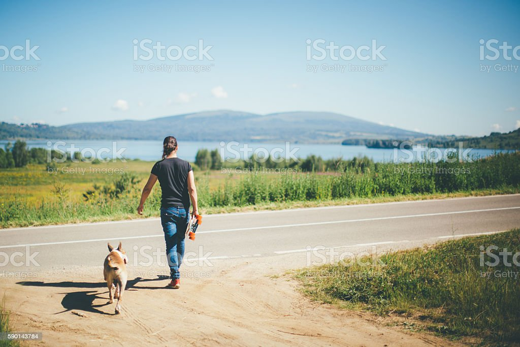 Man with longboard and his bull terrier stock photo
