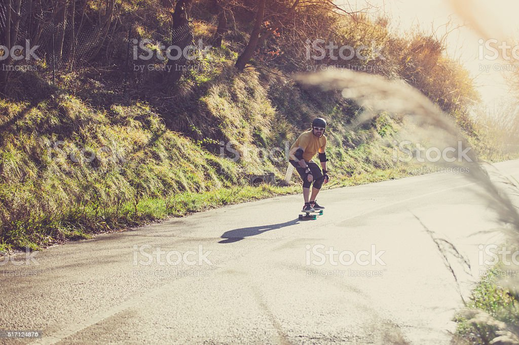 Man with longboard on country road stock photo