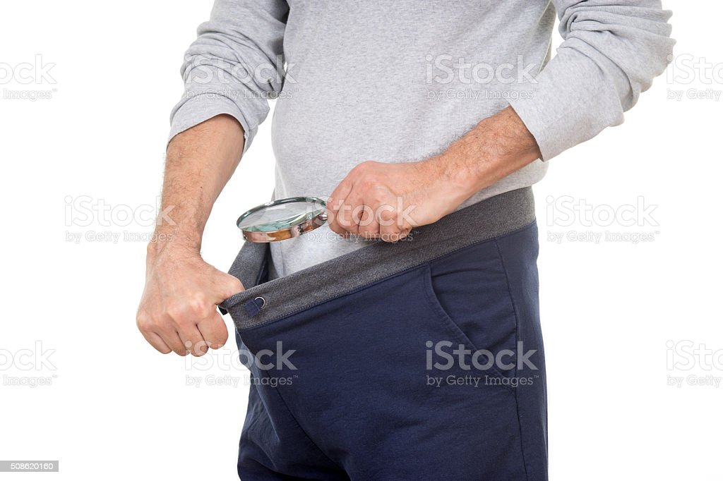 Man with magnifying glass looking into his tracksuit pants stock photo