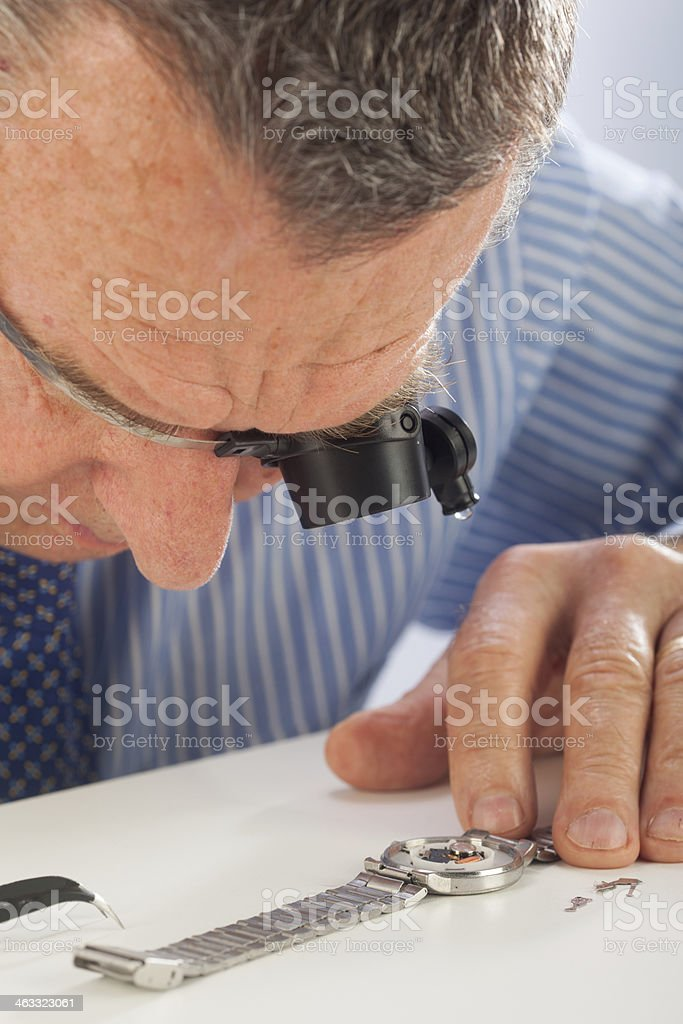 Man with Magnifying Glasses Fixing Watch royalty-free stock photo
