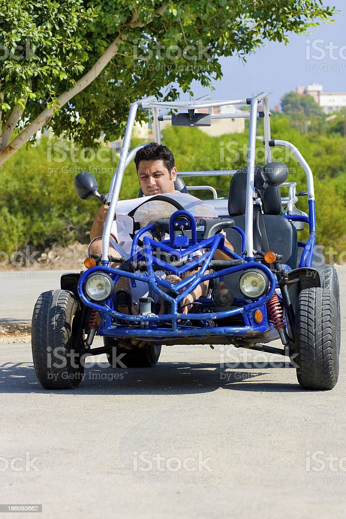 Man with map sits in buggy royalty-free stock photo