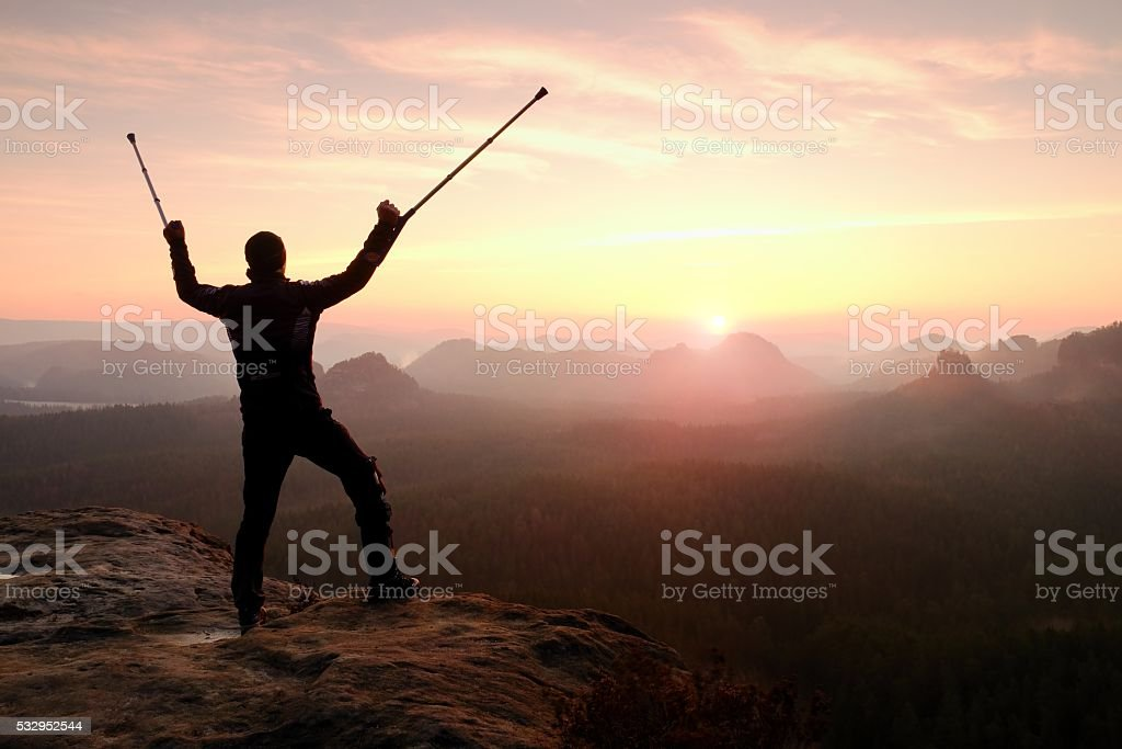 Man with  medicine pole above head stay on peak. stock photo